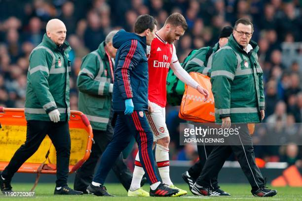Arsenal's English defender Calum Chambers is helped off the pitch with an injury during the English Premier League football match between Arsenal and...