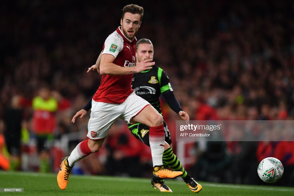 Arsenal's English defender Calum Chambers runs away from Doncaster Rovers' English striker Alfie May during the English League Cup third round football match between Arsenal and Doncaster Rovers at The Emirates Stadium in London on September 20, 2017. / AFP PHOTO / Ben STANSALL / RESTRICTED TO EDITORIAL USE. No use with unauthorized audio, video, data, fixture lists, club/league logos or 'live' services. Online in-match use limited to 75 images, no video emulation. No use in betting, games or single club/league/player publications. /