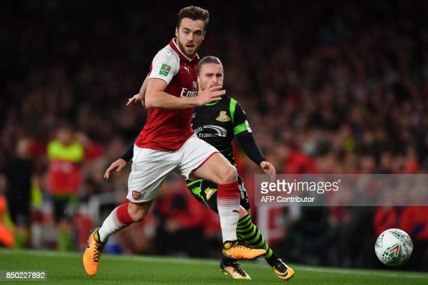 Arsenal's English defender Calum Chambers runs away from Doncaster Rovers' English striker Alfie May during the English League Cup third round...