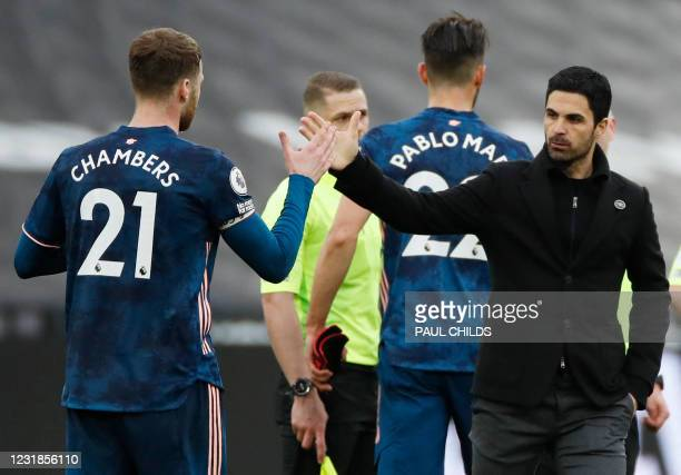 Arsenal's English defender Calum Chambers shakes hands with Arsenal's Spanish manager Mikel Arteta after the English Premier League football match...