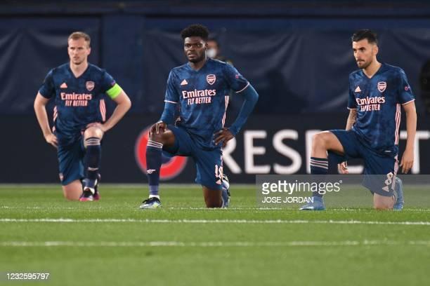 Arsenal's English defender Rob Holding, Arsenal's Ghanaian midfielder Thomas Partey and Arsenal's Spanish midfielder Dani Ceballos take a knee before...