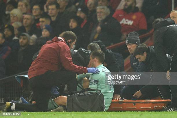 Arsenal's English defender Rob Holding recieves attention at the side of the pitch for an injury before being stretchered off during the English...