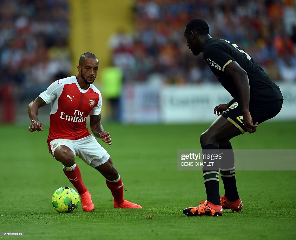 Arsenal's English forward Theo Walcott (L) vies with French Lens's defender Abdoul Ba during the football match Lens versus Arsenal on July 22 2016, at the Felix Bollaert stadium in Lens. / AFP / DENIS