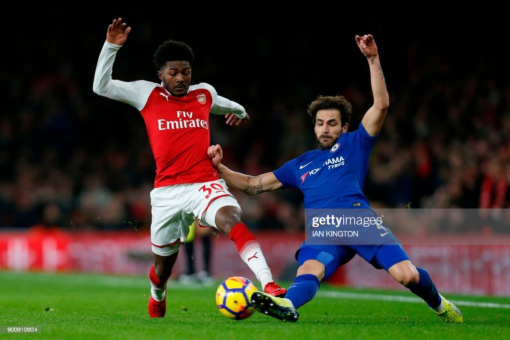 Arsenal's English midfielder Ainsley Maitland-Niles (L) tackles Chelsea's Spanish midfielder Cesc Fabregas during the English Premier League football match between Arsenal and Chelsea at the Emirates Stadium in London on January 3, 2018. / AFP PHOTO / Ian KINGTON / RESTRICTED TO EDITORIAL USE. No use with unauthorized audio, video, data, fixture lists, club/league logos or 'live' services. Online in-match use limited to 75 images, no video emulation. No use in betting, games or single club/league/player publications. /