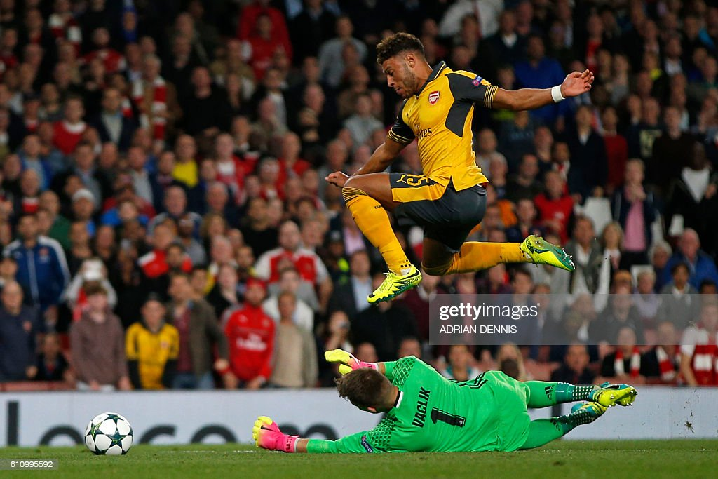 TOPSHOT - Arsenal's English midfielder Alex Oxlade-Chamberlain (up) vies with Basel's Czech goalkeeper Tomas Vaclik during the UEFA Champions League Group A football match between Arsenal and FC Basel at The Emirates Stadium in London on September 28, 2016. Arsenal won the game 2-0. / AFP / Adrian DENNIS