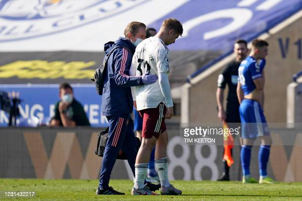 Arsenal's English midfielder Emile Smith Rowe is helped from the pitch after picking up an injury during the English Premier League football match...