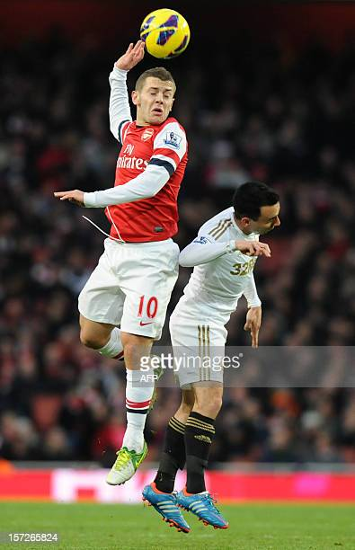 Arsenal's English midfielder Jack Wilshere jumps for a high ball against Swansea City's English midfielder Leon Britton during the English Premier...