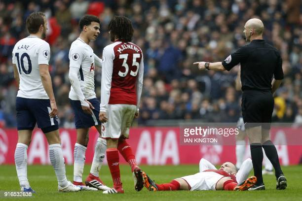 Arsenal's English midfielder Jack Wilshere lies on the pitch after a challenge by Tottenham Hotspur's Belgian midfielder Mousa Dembele during the...