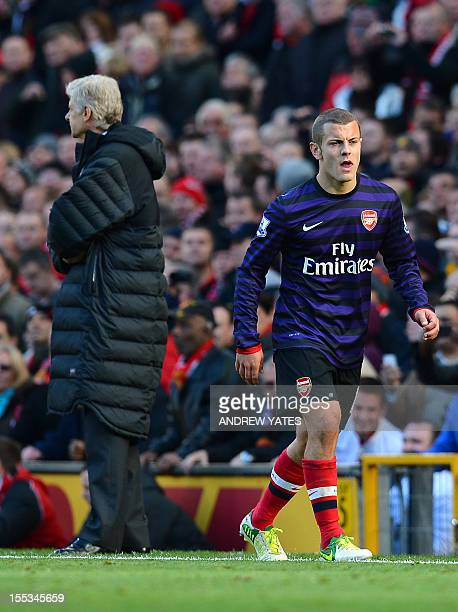 Arsenal's English midfielder Jack Wilshere walks past Arsenal's French manager Arsene Wenger after being sent off during the English Premier League...