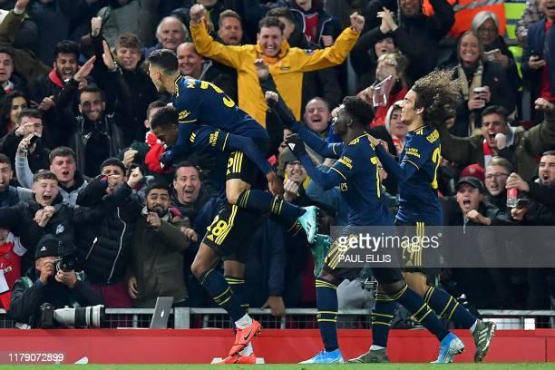 Arsenal's English midfielder Joe Willock celebrates scoring his team's fifth goal with Arsenal's Brazilian striker Gabriel Martinelli during the...