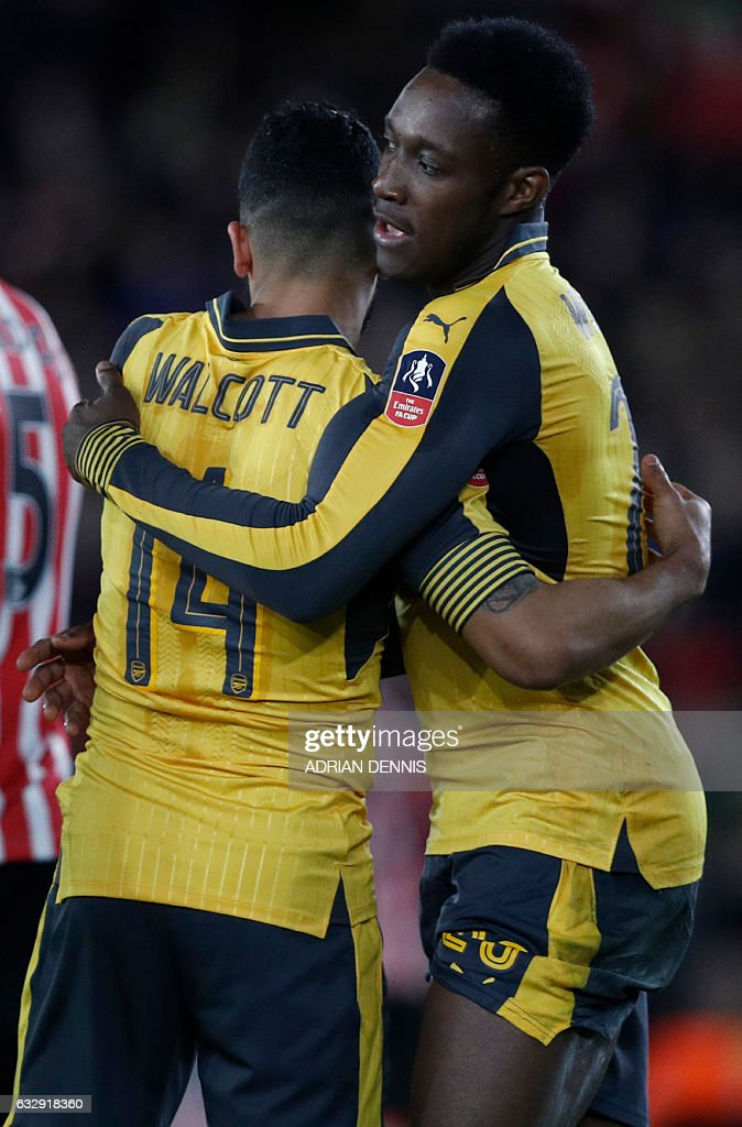 Arsenal's English midfielder Theo Walcott (L) celebrates scoring his team's third goal with Arsenal's English striker Danny Welbeck during the English FA Cup fourth round football match between Southampton and Arsenal at St Mary's in Southampton, southern England on January 28, 2017. / AFP / Adrian DENNIS / RESTRICTED TO EDITORIAL USE. No use with unauthorized audio, video, data, fixture lists, club/league logos or 'live' services. Online in-match use limited to 75 images, no video emulation. No use in betting, games or single club/league/player publications. /