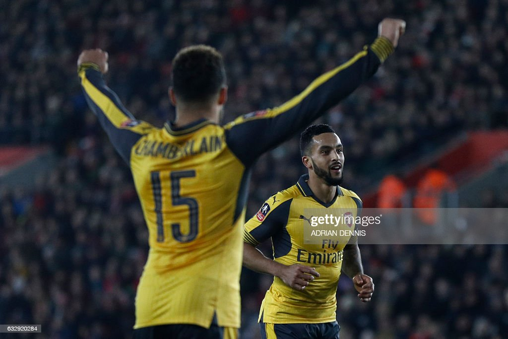 Arsenal's English midfielder Theo Walcott (R) celebrates scoring his team's fourth goal with Arsenal's English midfielder Alex Oxlade-Chamberlain during the English FA Cup fourth round football match between Southampton and Arsenal at St Mary's in Southampton, southern England on January 28, 2017. / AFP / Adrian DENNIS / RESTRICTED TO EDITORIAL USE. No use with unauthorized audio, video, data, fixture lists, club/league logos or 'live' services. Online in-match use limited to 75 images, no video emulation. No use in betting, games or single club/league/player publications. /