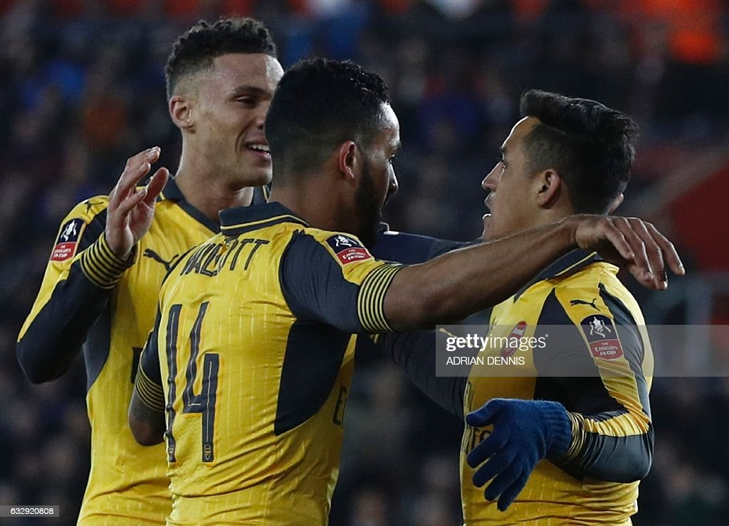 Arsenal's English midfielder Theo Walcott (C) celebrates scoring his team's fourth goal with Arsenal's Chilean striker Alexis Sanchez (R) during the English FA Cup fourth round football match between Southampton and Arsenal at St Mary's in Southampton, southern England on January 28, 2017. / AFP / Adrian DENNIS / RESTRICTED TO EDITORIAL USE. No use with unauthorized audio, video, data, fixture lists, club/league logos or 'live' services. Online in-match use limited to 75 images, no video emulation. No use in betting, games or single club/league/player publications. /