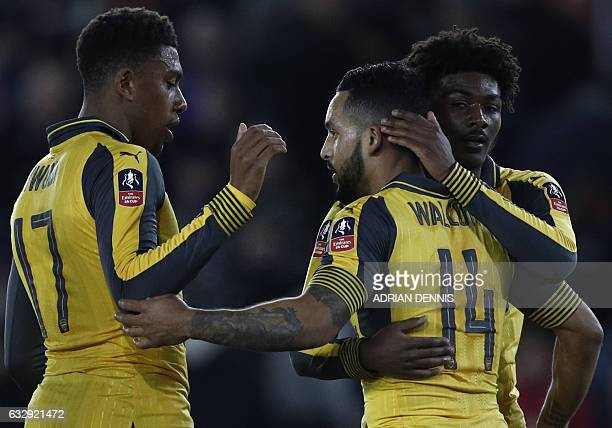 Arsenal's English midfielder Theo Walcott celebrates scoring his team's fifth goal with Arsenal's Nigerian striker Alex Iwobi and Arsenal's English...