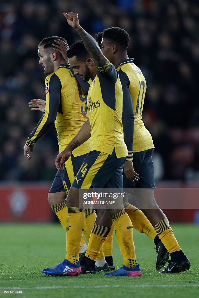 Arsenal's English midfielder Theo Walcott (C) celebrates scoring his team's fifth goal during the English FA Cup fourth round football match between Southampton and Arsenal at St Mary's in Southampton, southern England on January 28, 2017. / AFP / Adrian DENNIS / RESTRICTED TO EDITORIAL USE. No use with unauthorized audio, video, data, fixture lists, club/league logos or 'live' services. Online in-match use limited to 75 images, no video emulation. No use in betting, games or single club/league/player publications. /