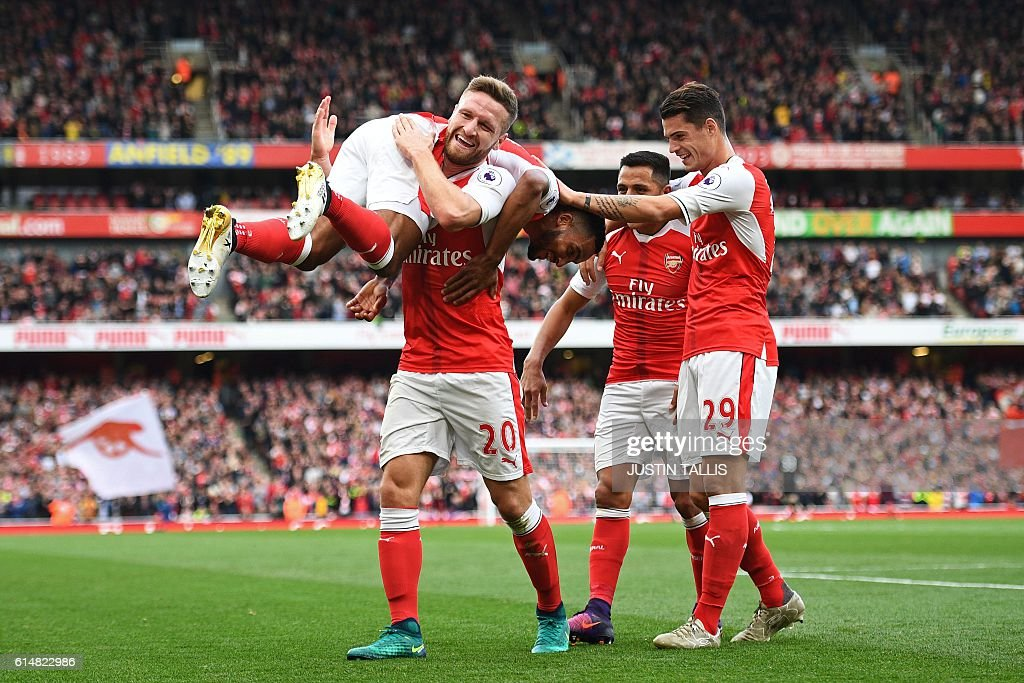 Arsenal's English midfielder Theo Walcott (L) celebrates with Arsenal's German defender Shkodran Mustafi (2nd L) Arsenal's Chilean striker Alexis Sanchez (2nd R) and Arsenal's Swiss midfielder Granit Xhaka (R) after scoring their second goal during the English Premier League football match between Arsenal and Swansea City at the Emirates Stadium in London on October 15, 2016. Arsenal won the game 3-2. / AFP / Justin TALLIS / RESTRICTED TO EDITORIAL USE. No use with unauthorized audio, video, data, fixture lists, club/league logos or 'live' services. Online in-match use limited to 75 images, no video emulation. No use in betting, games or single club/league/player publications. /