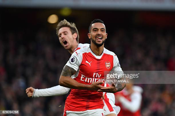 Arsenal's English midfielder Theo Walcott celebrates with Arsenal's Spanish defender Nacho Monreal after scoring their second goal during the English...
