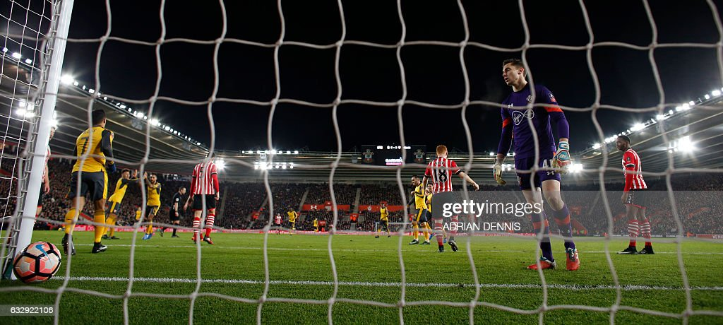 Arsenal's English midfielder Theo Walcott (3R) celebrates with Arsenal's English midfielder Alex Oxlade-Chamberlain (2L) after scoring his team's fourth goal past Southampton's English goalkeeper Harry Lewis during the English FA Cup fourth round football match between Southampton and Arsenal at St Mary's in Southampton, southern England on January 28, 2017. Arsenal won the match 5-0. / AFP / Adrian DENNIS / RESTRICTED TO EDITORIAL USE. No use with unauthorized audio, video, data, fixture lists, club/league logos or 'live' services. Online in-match use limited to 75 images, no video emulation. No use in betting, games or single club/league/player publications. /