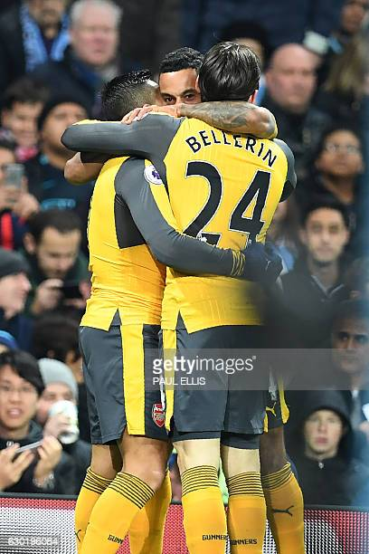 Arsenal's English midfielder Theo Walcott celebrates with teammates after scoring the opening goal of the English Premier League football match...