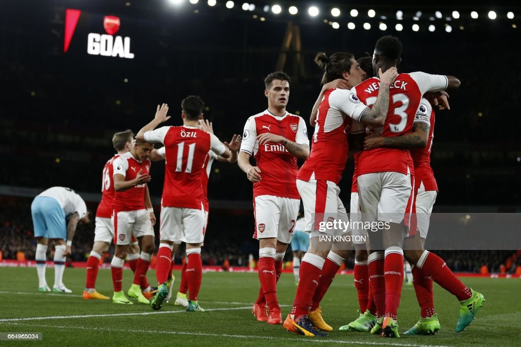 Arsenal's English midfielder Theo Walcott celebrates with teammates after scoring their second goal during the English Premier League football match between Arsenal and West Ham United at the Emirates Stadium in London on April 5, 2017. / AFP PHOTO / Ian KINGTON / RESTRICTED TO EDITORIAL USE. No use with unauthorized audio, video, data, fixture lists, club/league logos or 'live' services. Online in-match use limited to 75 images, no video emulation. No use in betting, games or single club/league/player publications. /