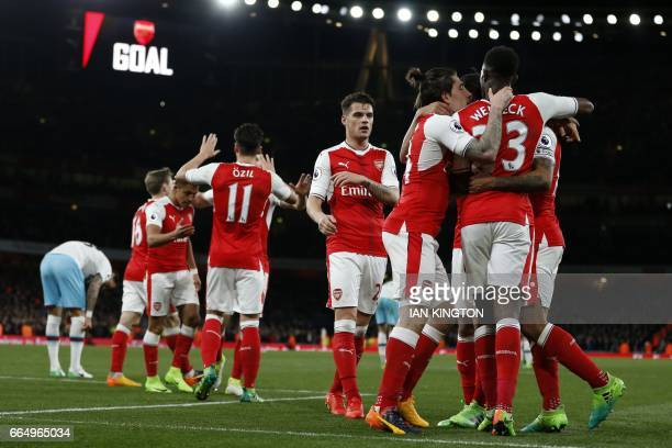 Arsenal's English midfielder Theo Walcott celebrates with teammates after scoring their second goal during the English Premier League football match...