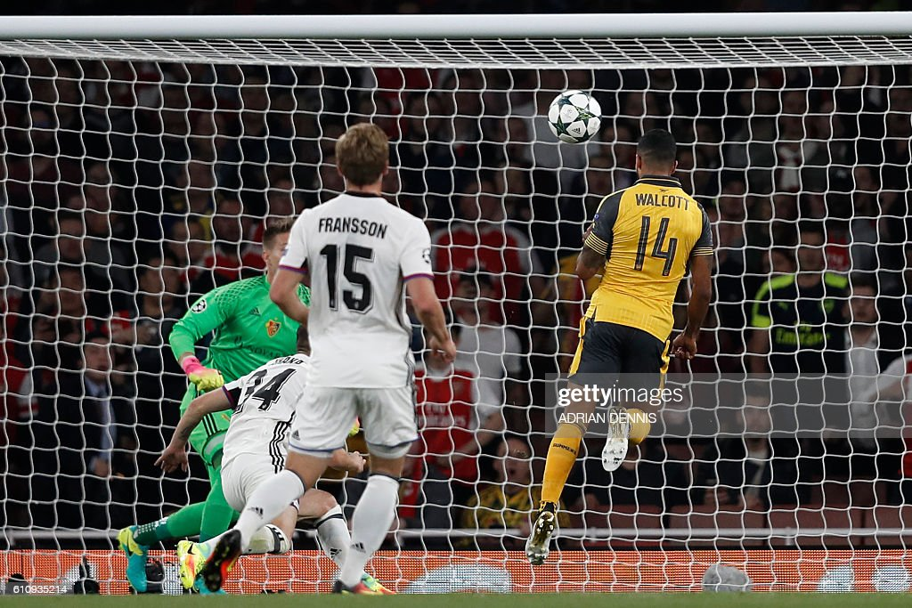 Arsenal's English midfielder Theo Walcott (R) heads the opening goal past Basel's Czech goalkeeper Tomas Vaclik (L) during the UEFA Champions League Group A football match between Arsenal and FC Basel at The Emirates Stadium in London on September 28, 2016. / AFP / Adrian DENNIS