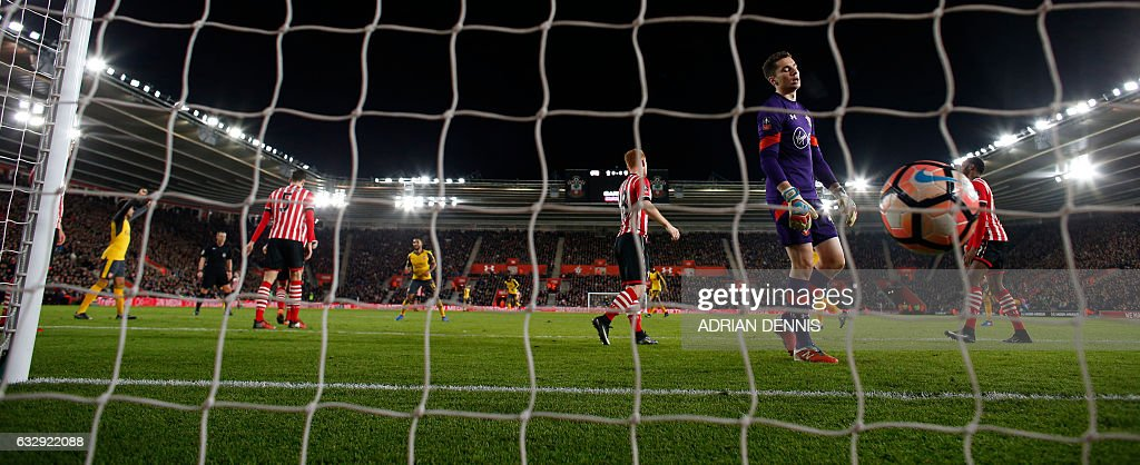 Arsenal's English midfielder Theo Walcott (C) reacts after scoring his team's fourth goal past Southampton's English goalkeeper Harry Lewis during the English FA Cup fourth round football match between Southampton and Arsenal at St Mary's in Southampton, southern England on January 28, 2017. Arsenal won the match 5-0. / AFP / Adrian DENNIS / RESTRICTED TO EDITORIAL USE. No use with unauthorized audio, video, data, fixture lists, club/league logos or 'live' services. Online in-match use limited to 75 images, no video emulation. No use in betting, games or single club/league/player publications. /