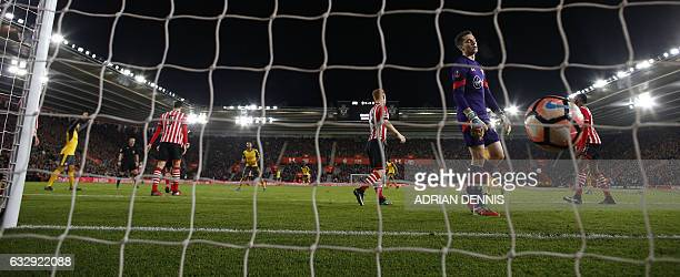 Arsenal's English midfielder Theo Walcott reacts after scoring his team's fourth goal past Southampton's English goalkeeper Harry Lewis during the...