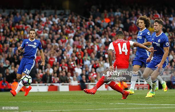 Arsenal's English midfielder Theo Walcott scores their second goal during the English Premier League football match between Arsenal and Chelsea at...