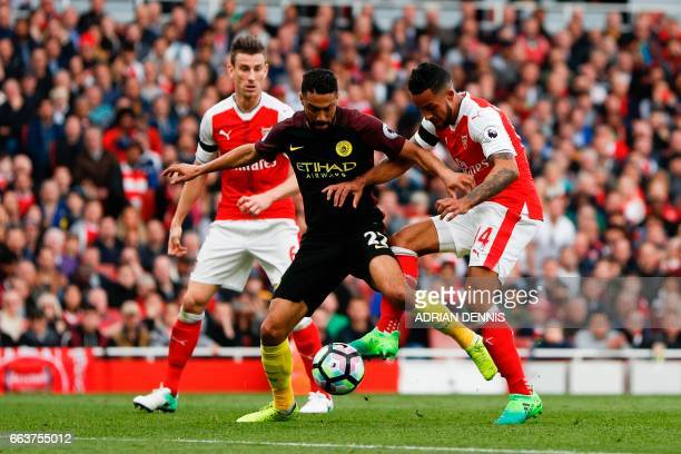 Arsenal's English midfielder Theo Walcott shoots between Manchester City's French defender Gael Clichy's leags to score their first goal during the...