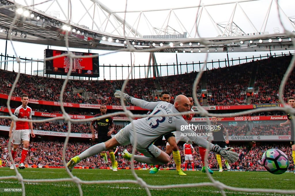 Arsenal's English midfielder Theo Walcott (centre hidden) watches his shot beat Manchester CIty's Argentinian goalkeeper Willy Caballero for Arsenal's first goal during the English Premier League football match between Arsenal and Manchester City at the Emirates Stadium in London on April 2, 2017. / AFP PHOTO / Adrian DENNIS / RESTRICTED TO EDITORIAL USE. No use with unauthorized audio, video, data, fixture lists, club/league logos or 'live' services. Online in-match use limited to 75 images, no video emulation. No use in betting, games or single club/league/player publications. /
