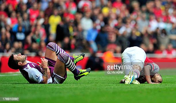 Arsenal's English striker Alex OxladeChamberlain and Aston Villa's Spanish defender Antonio Luna lie on the floor after a tackle during their English...