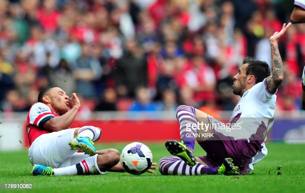 Arsenal's English striker Alex OxladeChamberlain is tackled by Aston Villa's Spanish defender Antonio Luna during their English Premier League...