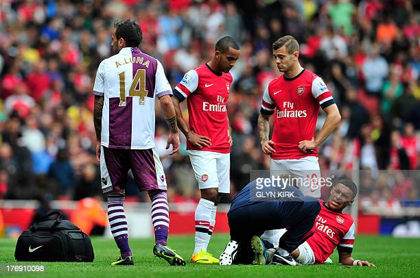 Arsenal's English striker Alex OxladeChamberlain is tended to after a tackle with Aston Villa's Spanish defender Antonio Luna during their English...
