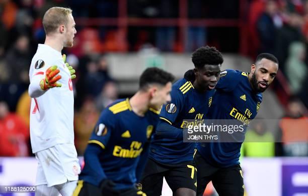 Arsenal's English striker Bukayo Saka celebrates with teammate Arsenal's French striker Alexandre Lacazette after scoring a goal during the UEFA...