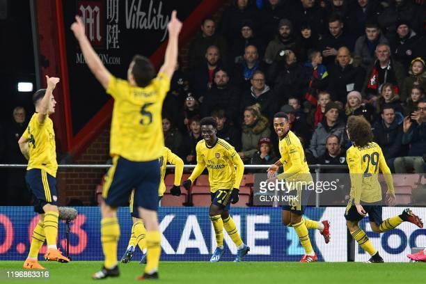 Arsenal's English striker Bukayo Saka celebrates with teammates after scoring the opening goal of the English FA Cup fourth round football match...