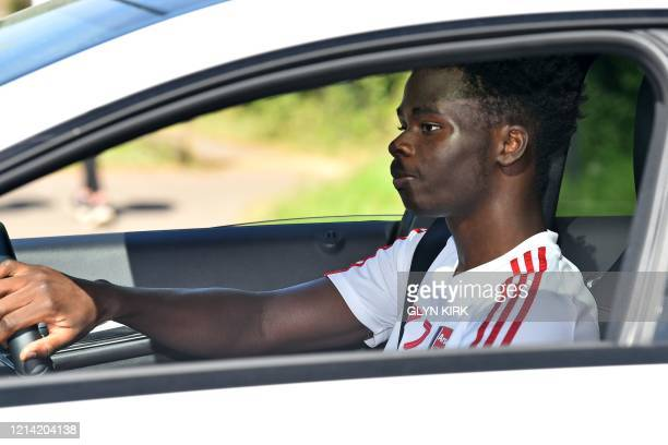 Arsenal's English striker Bukayo Saka leaves Arsenal's Colney training centre north of London on May 20 2020 as training continues for Premier League...