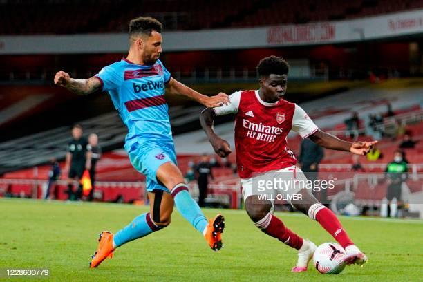 Arsenal's English striker Bukayo Saka plays the ball as West Ham United's English defender Ryan Fredericks defends during the English Premier League...