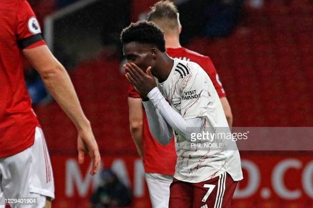 Arsenal's English striker Bukayo Saka reacts after missing a good chance during the English Premier League football match between Manchester United...