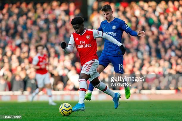 Arsenal's English striker Bukayo Saka runs away from Chelsea's English midfielder Mason Mount during the English Premier League football match...
