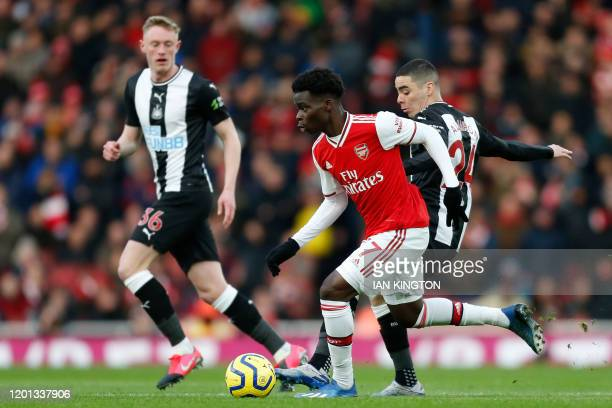 Arsenal's English striker Bukayo Saka vies with Newcastle United's Paraguayan midfielder Miguel Almiron during the English Premier League football...