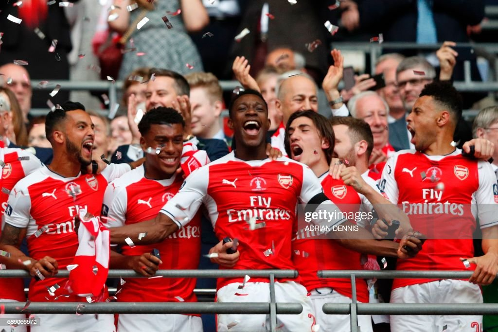 Arsenal's English striker Danny Welbeck (C) and Arsenal players celebrate their victory over Chelsea in the English FA Cup final football match between Arsenal and Chelsea at Wembley stadium in London on May 27, 2017. Aaron Ramsey scored a 79th-minute header to earn Arsenal a stunning 2-1 win over Double-chasing Chelsea on Saturday and deliver embattled manager Arsene Wenger a record seventh FA Cup. / AFP PHOTO / Adrian DENNIS / NOT