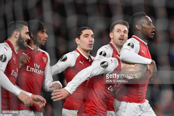 TOPSHOT Arsenal's English striker Danny Welbeck celebrates with teammates scoring the team's third goal during the UEFA Europa League round of 16...
