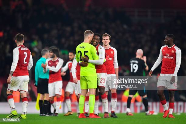 Arsenal's English striker Danny Welbeck embraces West Ham United's English goalkeeper Joe Hart at the end of the English League Cup quarterfinal...