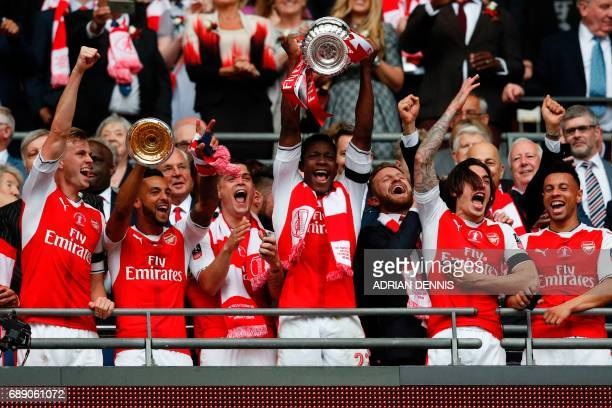 Arsenal's English striker Danny Welbeck lifts the FA Cup trophy as Arsenal players celebrate their victory over Chelsea in the English FA Cup final...