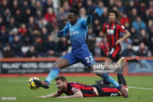 Arsenal's English striker Danny Welbeck takesa chance at goal after a challenge by Bournemouth's English defender Simon Francis during the English...