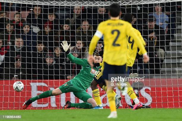 Arsenal's Englsih striker Eddie Nketiah slots the ball past Bournemouth's English goalkeeper Mark Travers for their second goal during the English FA...