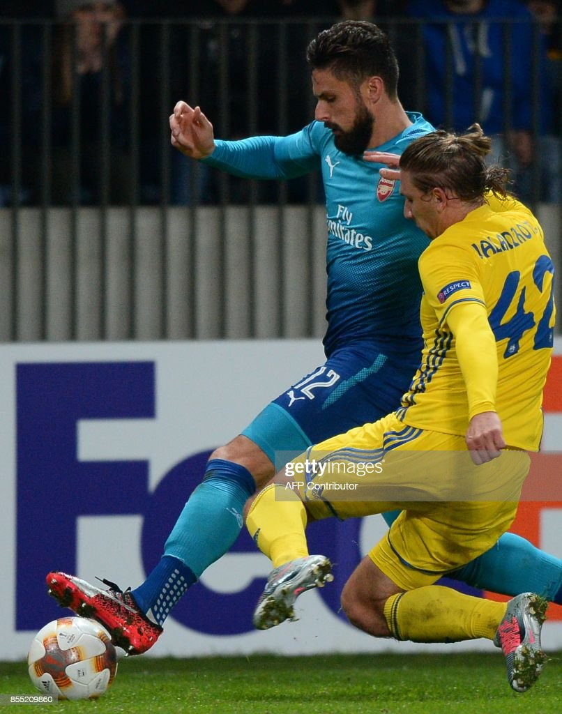 Arsenal's forward from France Olivier Giroud (L) and BATE Borisov's defender from Belarus Maksim Valadzko vie for the ball during the UEFA Europa League Group H football match between FC BATE Borisov and Arsenal FC in Borisov, outside Minsk, on September 28, 2017. / AFP PHOTO / Maxim MALINOVSKY