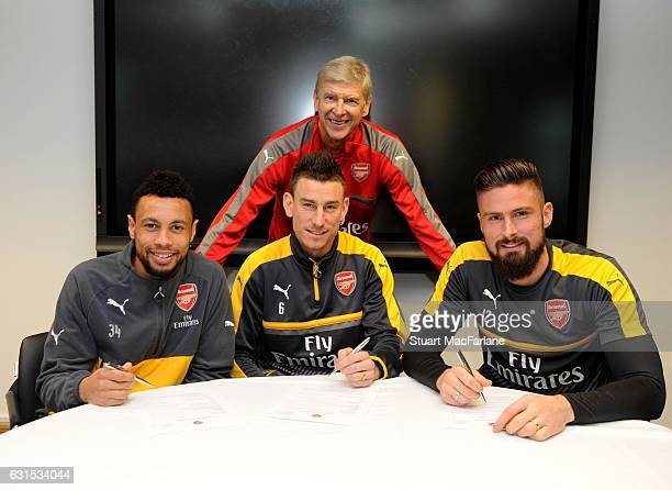 Arsenal's Francis Coquelin, Laurent Koscielny and Olivier Giroud sign their new contracts with manager Arsene Wenger at London Colney on January 5,...