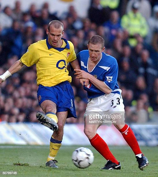 Arsenal's Freddie Ljunberg clears from Portsmouth's John Curtis 04 May 2004 during their league match in Portsmouth AFP PHOTO/ Martyn HAYHOW